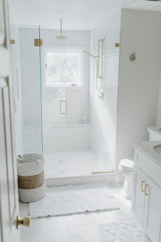 a small and chic white bathroom with fish scale tiles and square ones, gold fixtures and a pretty basket for laundry