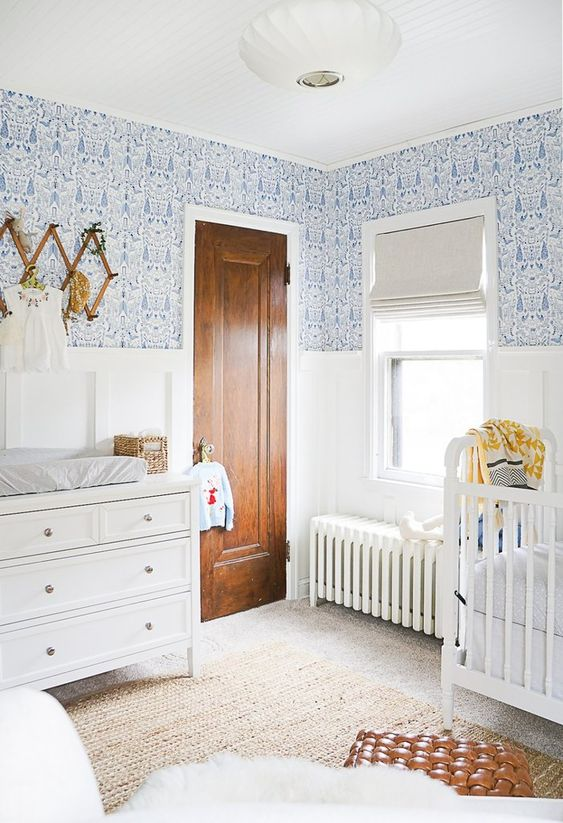 a stylish and beautiful white and blue nursery with printed wallpaper, white furniture and a leather ottoman
