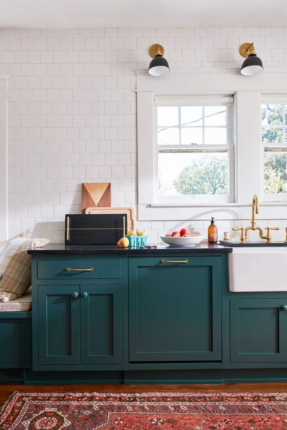 a stylish mid-century modern teal kitchen with black countertops, a white tile wall and touches of gold here and there
