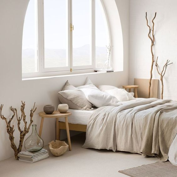 a Japandi bedroom with an arched window, light stained wooden furniture, grey and white bedding, driftwood