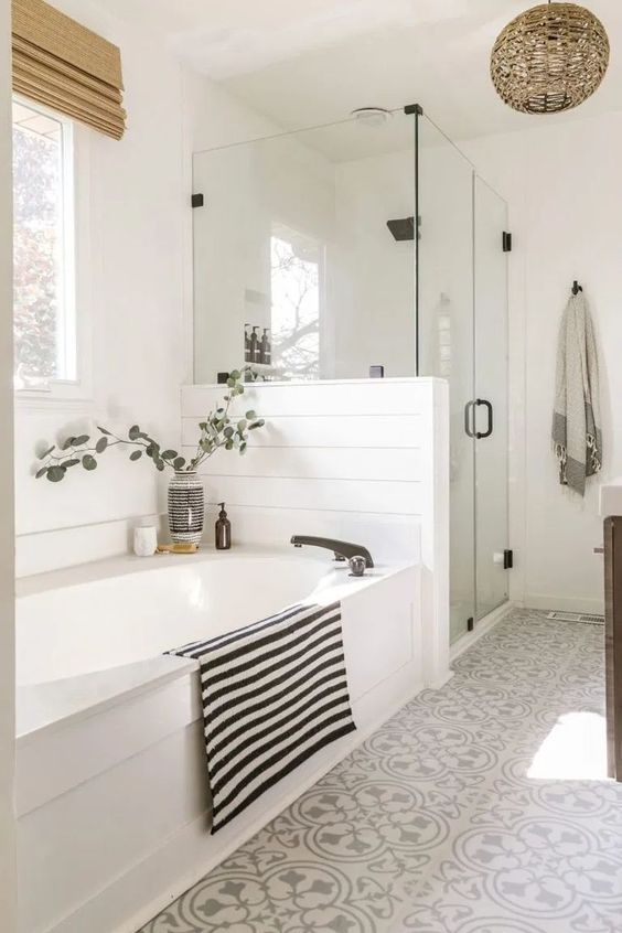 a boho farmhouse bathroom in white, with beadboard and patterned tiles, a shower space and a tub and shades