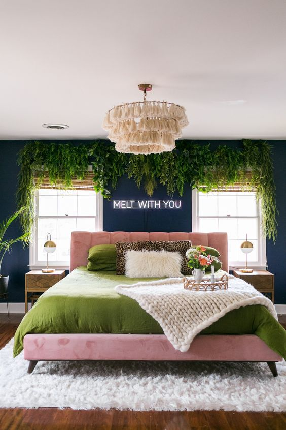 a jaw-dropping teal bedroom with hanging greenery, a pink bed and green bedding and a tassel chandelier