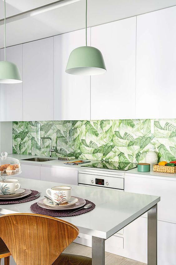 a minimalist white kitchen with a tropical leaf backsplash, green pendant lamps and touches of green here and there