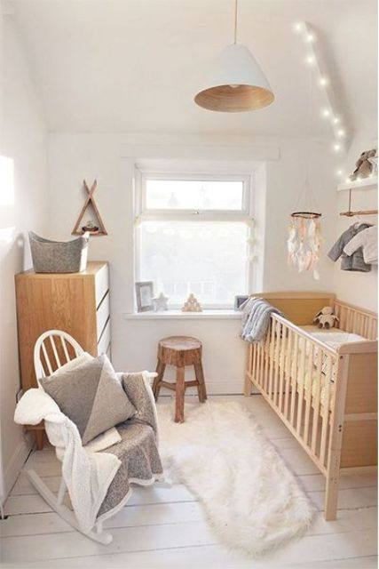 a neutral hygge nursery with light-stained wooden furniture, lights, a crib and a pendant lamp