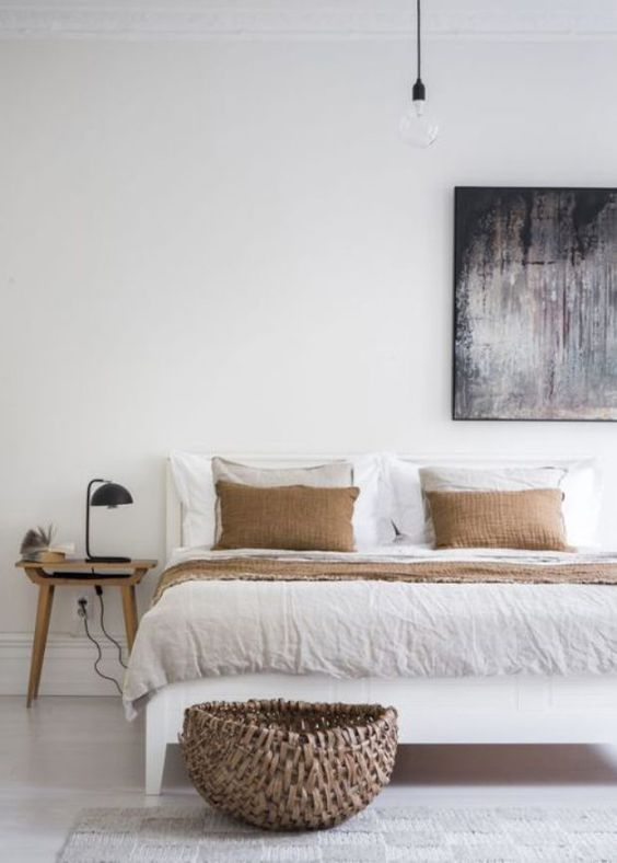 a Japandi bedroom with wooden and white furniture, a bold artwork, terracotta and white bedding and a basket