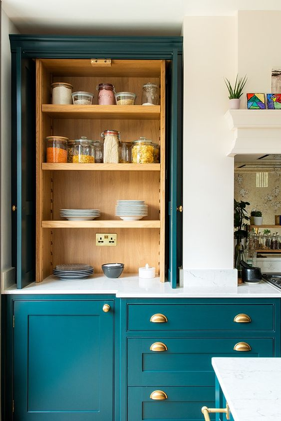 a chic teal kitchen with elegant cabinetry, light-stained wooden compartments, gold fixtures and white stone countertops