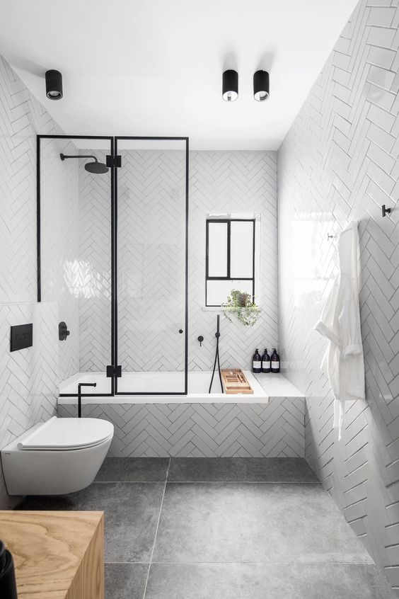 a contemporary bathroom with glossy white tiles, large scale tiles on the floor, black fixtures and a window for more light
