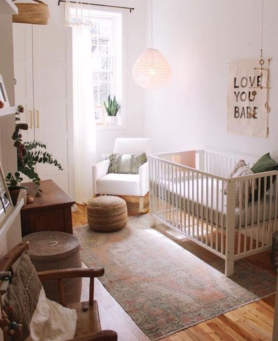 a hygge nursery with white furniture, a jute ottoman and a basket, a pendant lamp and a wooden chair