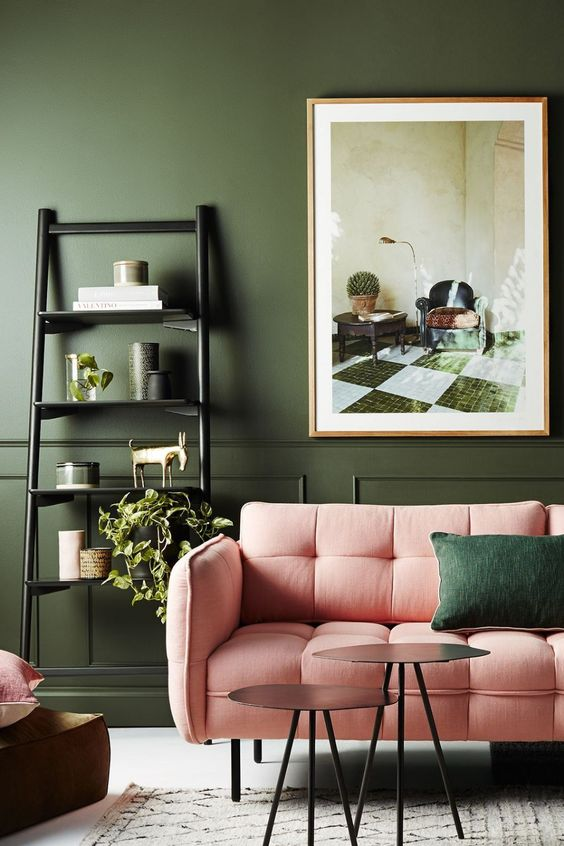 a refined and chic living room with dark green walls softened with pink furniture, catchy tables and potted plants
