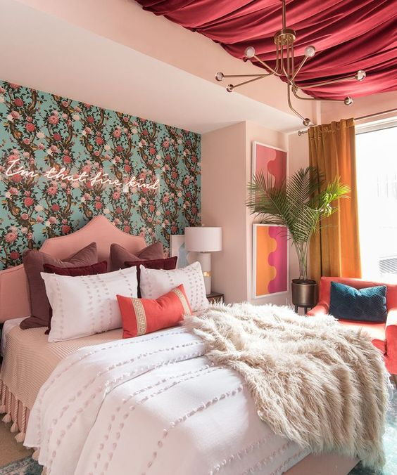 an eye-catchy bedroom with floral wallpaper and a neon sign, a pink draped ceiling, bright textiles and artworks