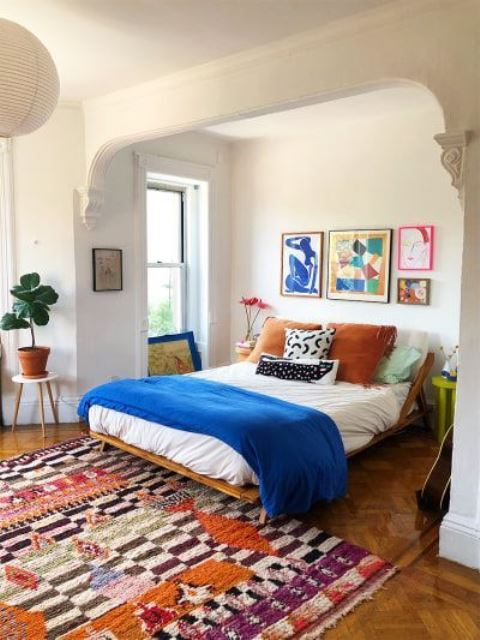 a colorful modern bedroom with a bright gallery wall, bold bedding and textiles and potted plants