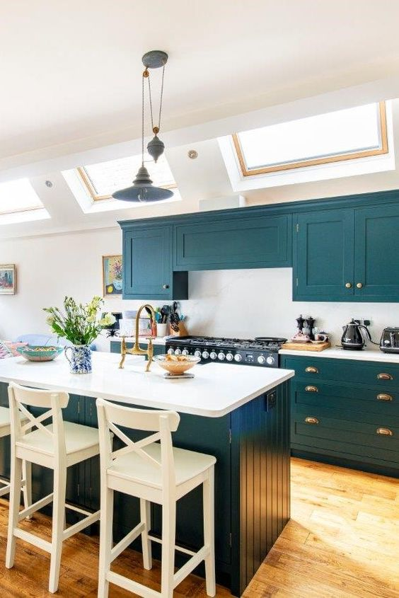 a lovely teal kitchen with a white backsplash and countertops, a matching kitchen island with white countertops and a backsplash