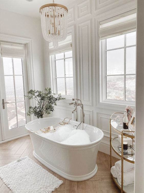 a luxurious white bathroom clad with panels, with a gorgeous view, a vintage tub, a gold and glass side table and a crystal chandelier