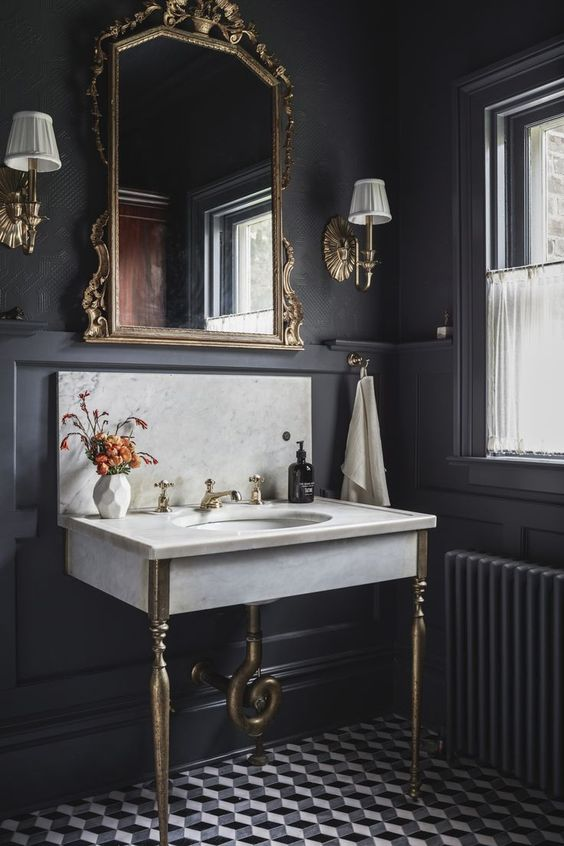 a moody old world bathroom with a diamond print floor, a marble sink, a refined mirror in a gold frame
