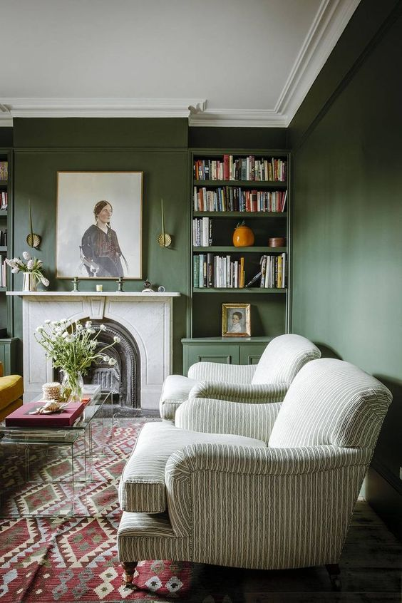a sophisticated green living room with dark walls, vintage and modern furniture, built in bookshelves and a fireplace