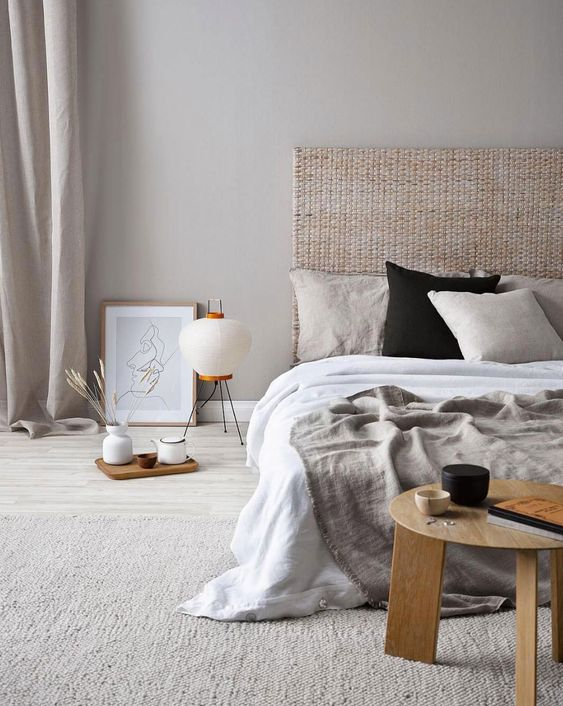 a stylish and welcoming Japandi bedroom with a rattan bed, wooden furniture, grey and white bedding and lamps