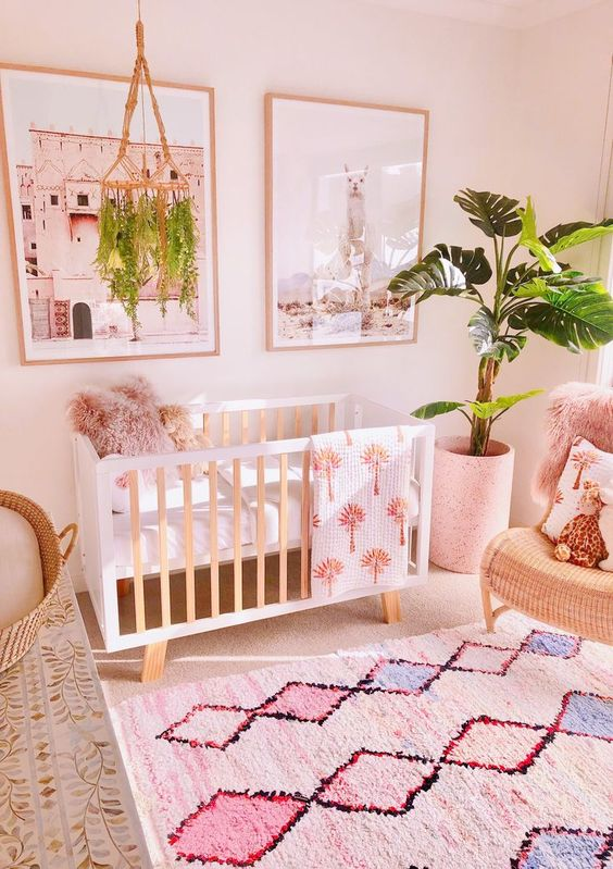 a tropical nursery with pink walls, printed rugs and towels, a potted plant and a matching mobile is cool