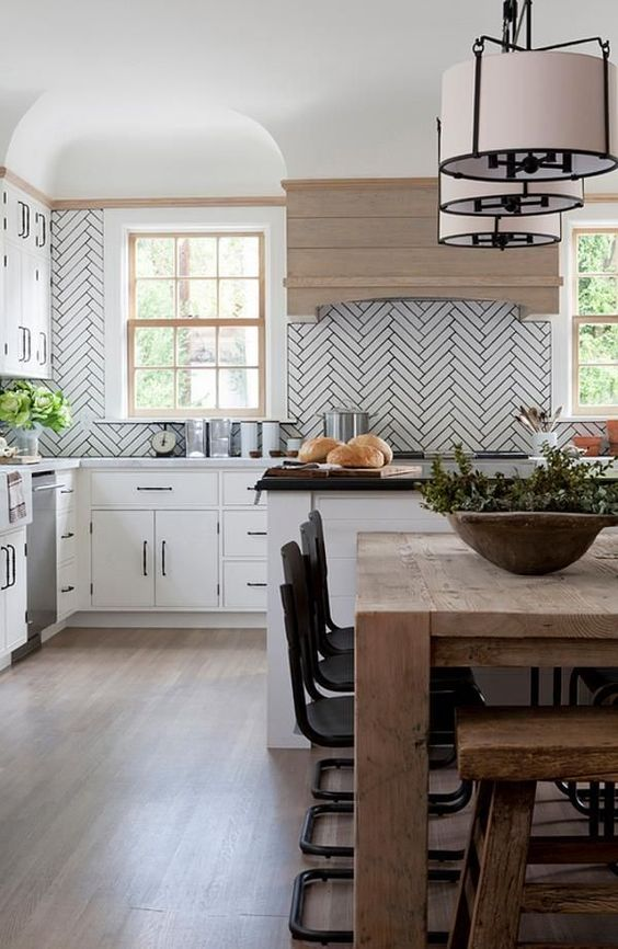 a white kitchen accented with white long tiles and grey grout plus a light stained wooden hood for more coziness