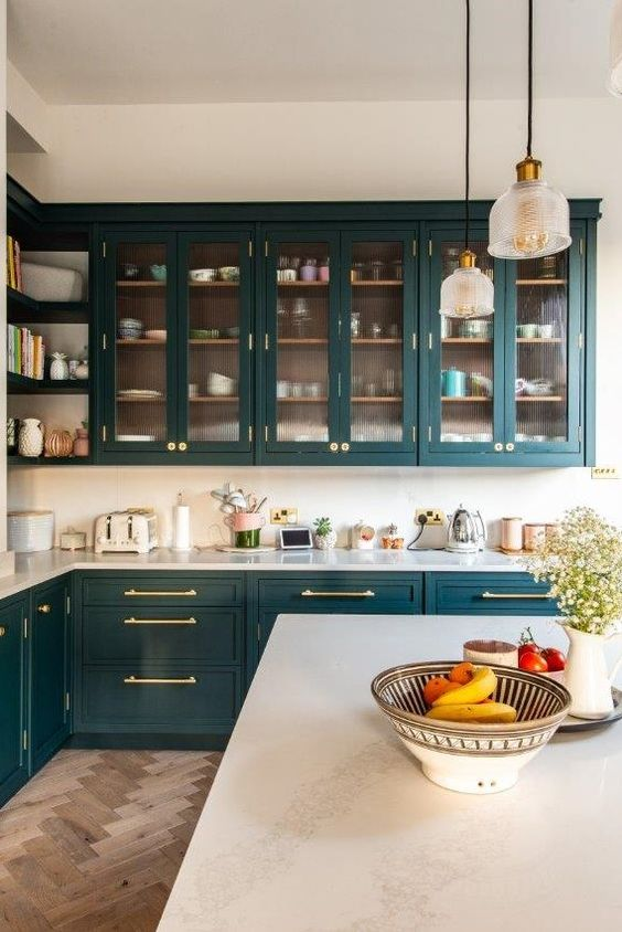 a chic and refined teal kitchen with glass and usual cabinets, white countertops and a white backsplash plus pendant lamps