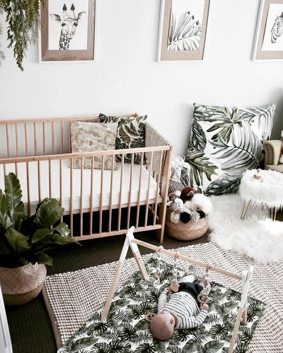 a neutral tropical nursery with light-stained wooden furniture, tropical print textiles and potted plants