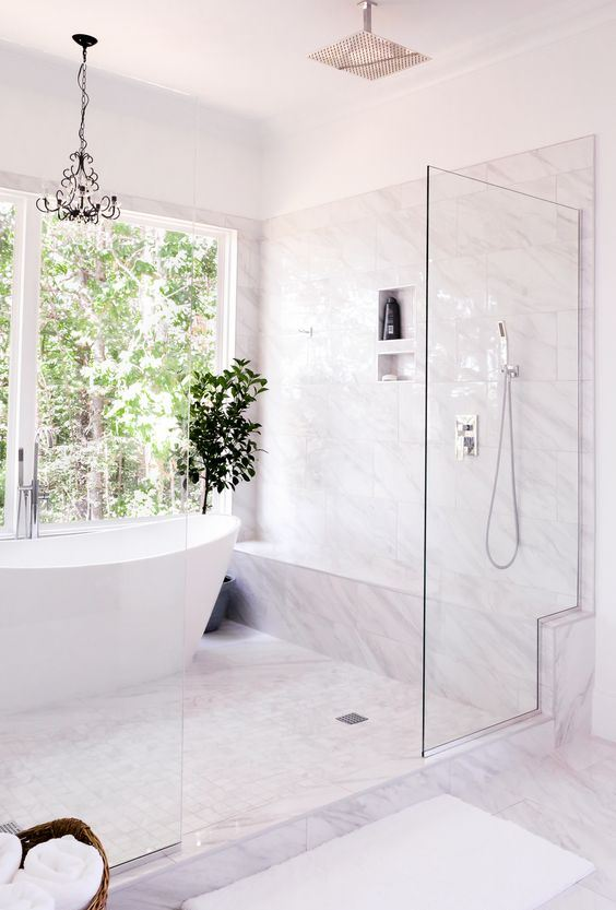 a refined modern bathroom clad with white marble, with a glass shower and a large window for the view