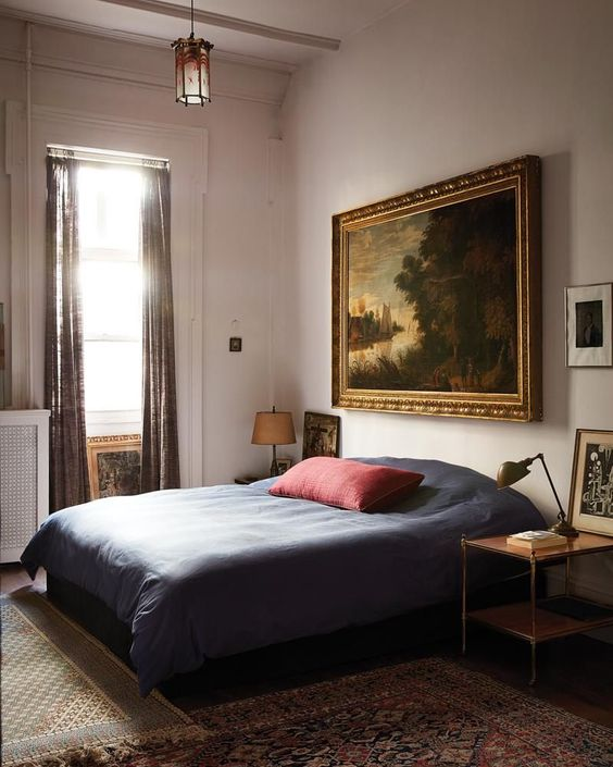 a refined old world bedroom with a comfy bed and nightstands, beautiful artworks, table lamps and printed textiles