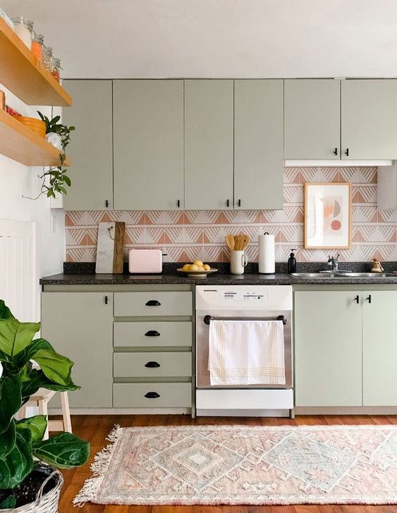 an olive green kitchen with black handles and a very eye catchy rust and white geometric print backsplash that stands out