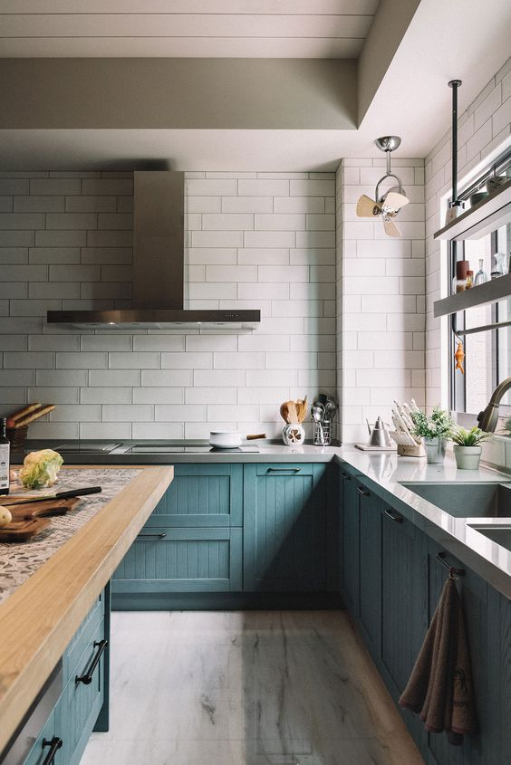 a catchy teal kitchen with vintage cabinets, a white tile backsplash, stone and butcherblock coutnertops and stainless steel fixtures