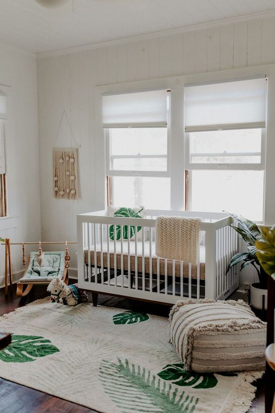 a neutral boho nursery with white and light-stained furniture, tropical prints, a boho ottoman and macrame
