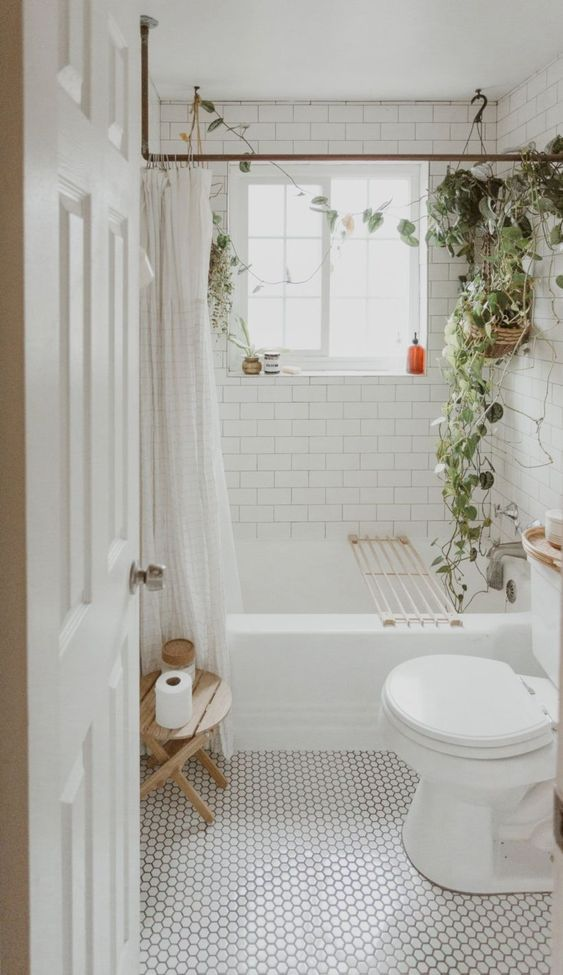 a small boho bathroom in white, with subway tiles, marble penny tiles and potted greenery to refresh the space