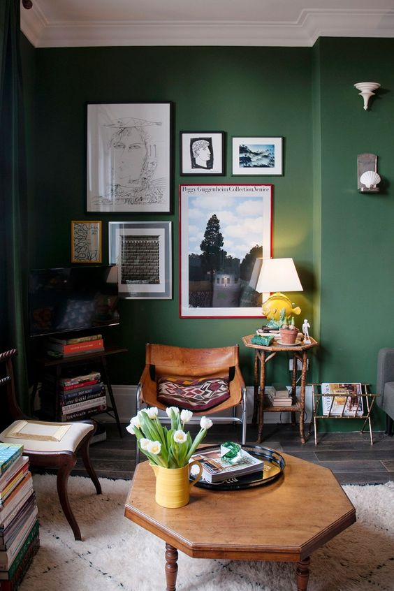 a stylish green living room with dark stained furniture, a gallery wall with bold art and printed pillows