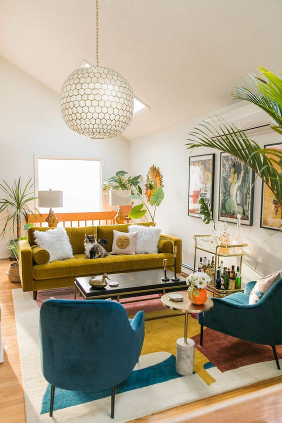 a vibrant mid-century modern living room in navy, white and mustard, with a colorful gallery wall and potted plants