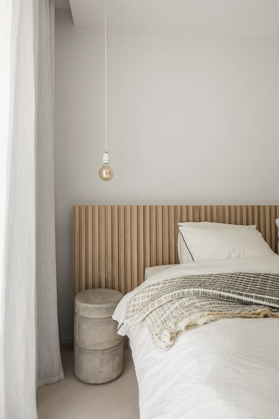 a chic bedroom with grey walls, a light stained bed, a concrete table and a pendant bulb