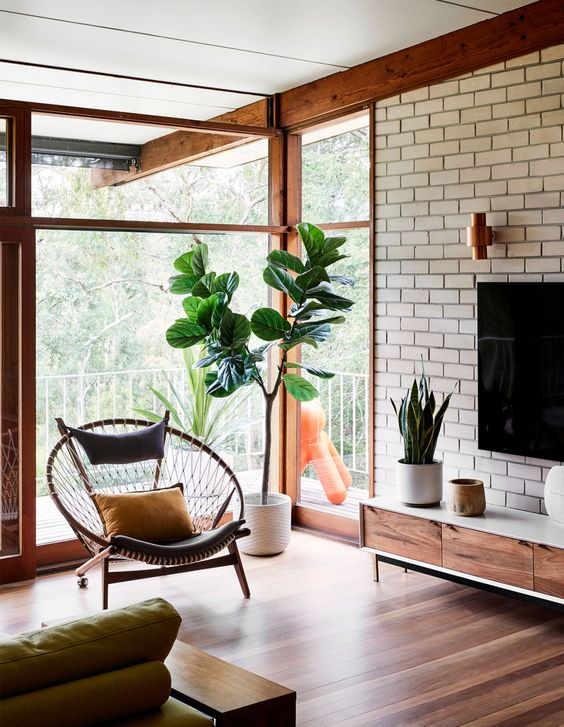a neutral mid century modern living room with a brick wall, glazed walls and elegant furniture
