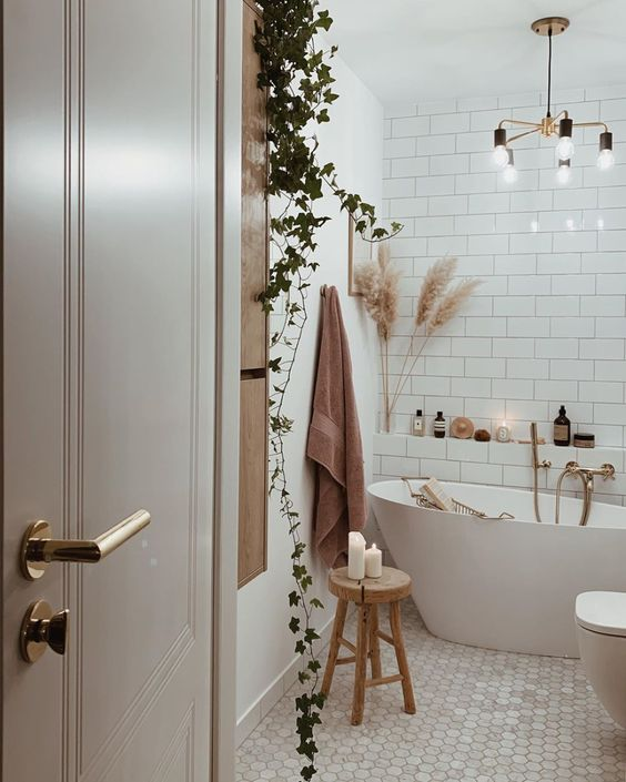 28 a pretty boho bathroom in white, with subway tiles, marble hex ones, an irregular tub and potted plants and a chandelier