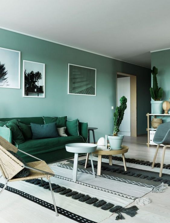 28 a serene monochromatic living room with light green walls, dark green furniture, wooden tables and potted plants