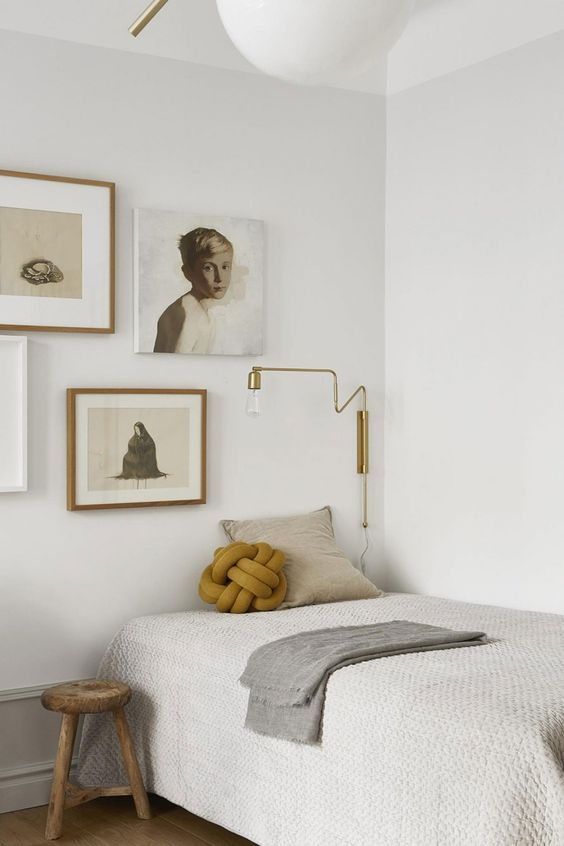 a Japandi guest bedroom in neutrals, with a gallery wall, a bed and a stool, a gold sconce and pretty pillows