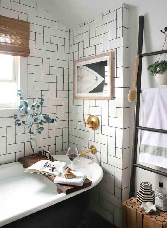 a chic neutral mid-century modern bathroom with a black vintage tub, a contrasting artwork and shades