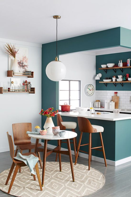 a modern teal kitchen separated from the rest of the space with a kitchen island, with a white tile backsplash and countertops