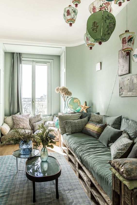 29 a monochromatic and eclectic green living room with light green walls, a dark green sofa, printed textiles and Asian lanterns