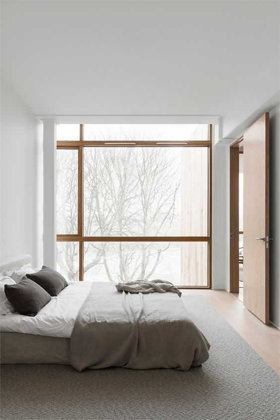 a minimalist Japandi bedroom in white and grey, with a glazed wall for a lovely view and light stained wooden floors