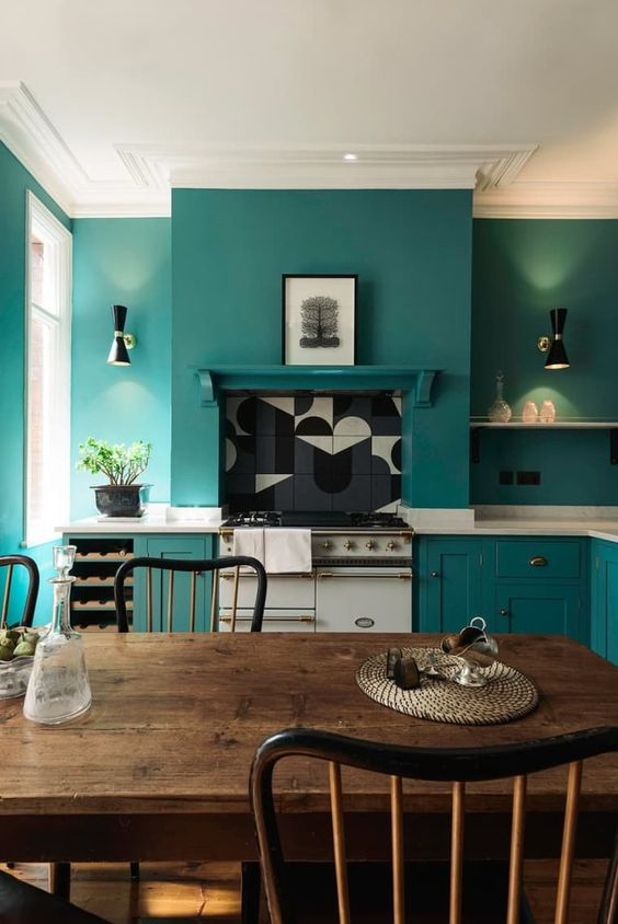 a teal kitchen with chic cabinets and matching walls for a sleek look, white stone countertops and a dining zone with vintage furniture