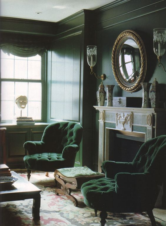 a moody living room in dark greens, with refined furniture, a fireplace, a large mirror and vintage vases