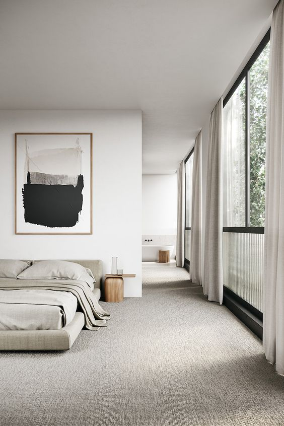 a welcoming and airy Japandi bedroom in light greys and white, with a statement artwork and grey bedding plus glazed walls