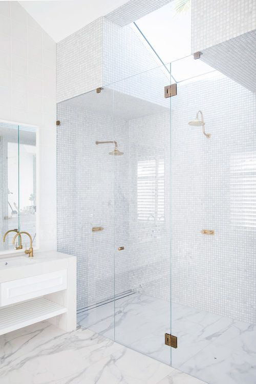 a welcoming white bathroom clad with tiles of various types, with a skylight and gold fixtures