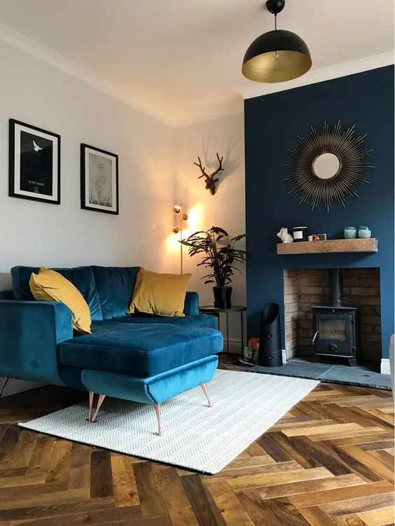 32 a pretty and stylish living room with navy furniture, a navy accented wall with a hearth and touches of gold is pretty