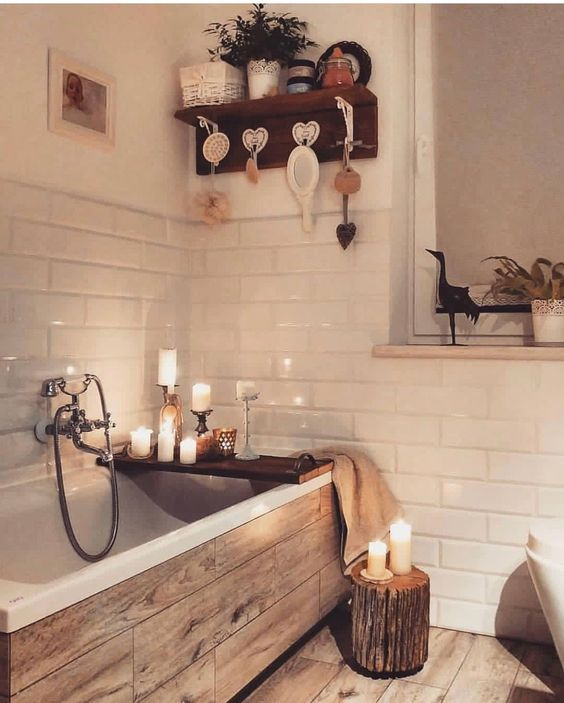 a pretty bathroom clad with white tiles and with wood print ones, with a tree stump and candles everywhere