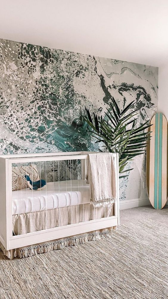 a surfing nursery with a unique water-inspired wall mural, a neutral crib and a surfing board