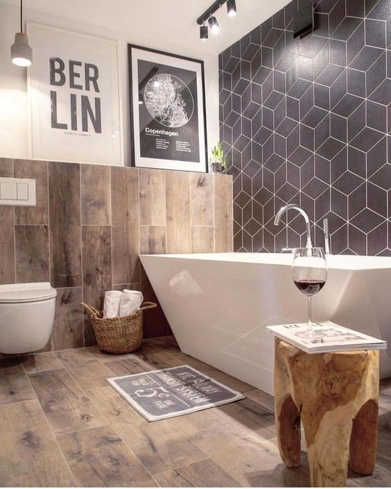 a chic bathroom with a navy geo tile wall, wood print tiles, a sculptural bathtub and a tree stump