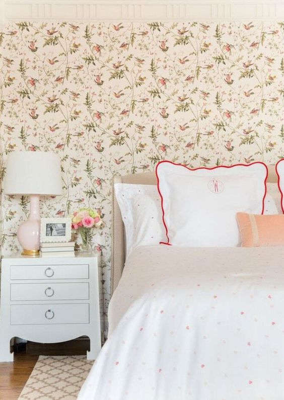 a cozy vintage-inspired bedroom with a floral wallpaper wall, polka dot bedding, vintage-inspired furniture and a blush lamp